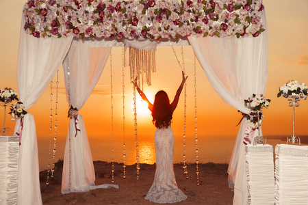 Sunset. bride silhouette. Wedding ceremony arch with flower arrangement and white curtain on cliff above sea, outdoor photo. Stock Photo