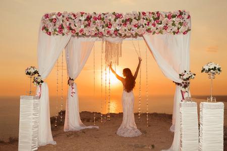 일몰. 신부 실루엣입니다. 꽃꽂이와 바다, 야외 여름 사진 위에 절벽에 흰색 커튼 결혼식 아치.