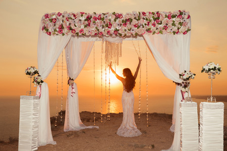 Zonsondergang. Bruids silhouet. Bruiloft ceremonie boog met bloem arrangement en wit gordijn op de klif boven de zee, buiten zomer foto.