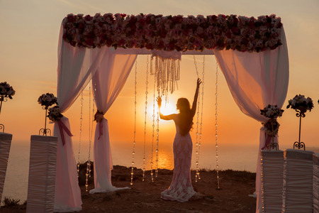 bride silhouette. Wedding ceremony arch with flower arrangement with white curtain at sunset above sea, outdoor photo. decor.