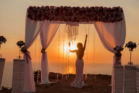 bruid silhouet. De ceremonieboog van het huwelijk met bloemstuk met wit gordijn bij zonsondergang boven overzees, openluchtfoto. decor.