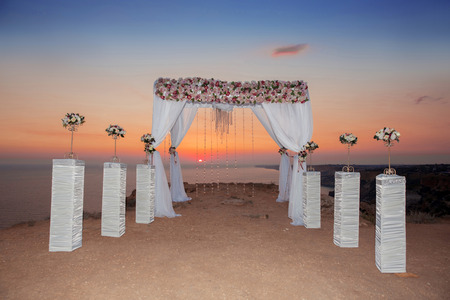 curtain background: Wedding ceremony arch with flower arrangement with white curtain on sunset, sunrise outdoor photo. decor. Stock Photo