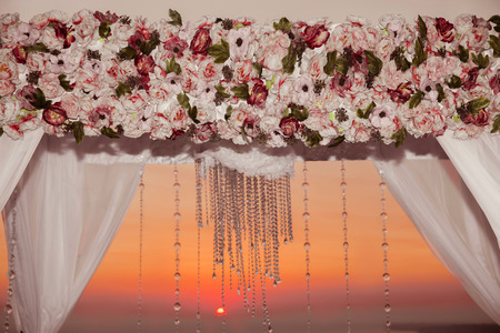 flower arrangement: Sunset. Wedding ceremony arch decor closeup with flower arrangement and crystals chandelier  decorated white curtain above sea, outdoor photo. decor.