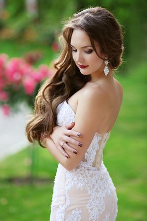 Belle brune Bride portrait de mariage, femme avec de longs cheveux ondulés porter en dentelle blanche robe de mariée posant dans un parc vert.
