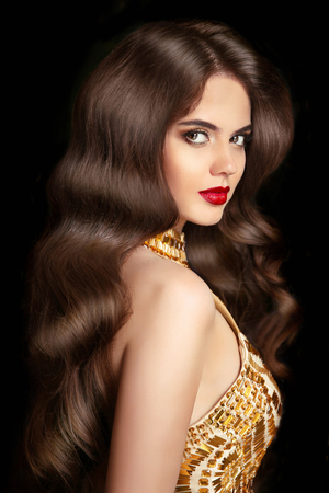 smooth: Hair. Makeup. Beautiful brunette girl with long wavy shiny hairstyle. Elegant woman with red lips and fashion golden jewelry isolated on black background.