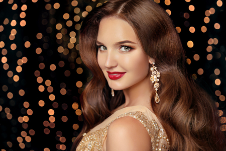 elegant party: Makeup. Elegant hairstyle. Beautiful brunette smiling with long wavy hair, red lips makeup and fashion jewelry earrings. Attractive girl isolated on holiday party lights background.