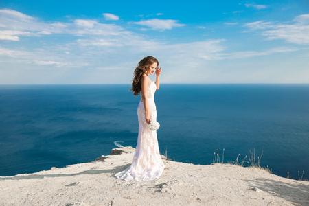 Bella sposa in abito nuziale all'aperto foto. paesaggio di sfondo.