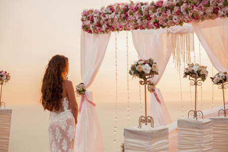 outdoor wedding: Beautiful bride on ceremony, brunette standing by wedding arch with flower arrangement with white curtain on sunset, outdoor photo.