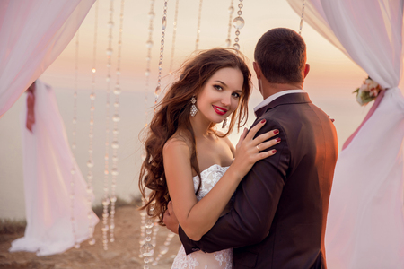 wedding portrait: wedding portrait of beautiful smiling Bride and Groom Under wedding Archway. newlyweds hugs and dancing under the wedding arch and altar against the sunset sky and seashore.