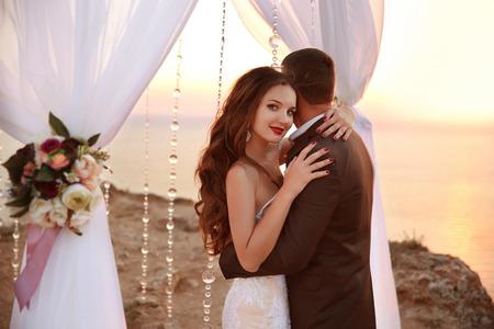 結婚式: 美しい笑顔の花嫁と新郎の下でウェディング アーチの結婚式の肖像画。新婚夫婦抱擁と結婚式のアーチと海岸の夕焼け空と祭壇の下で踊っています 写真素材
