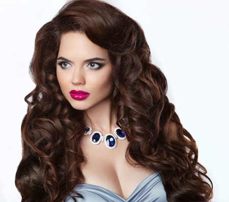 edelstenen: Long hair. Makeup. Beautiful brunette woman with sensual red lips and curly hairstyle, expensive gems jewelry. Girl model isolated on studio white background. Elegant lady. Stockfoto