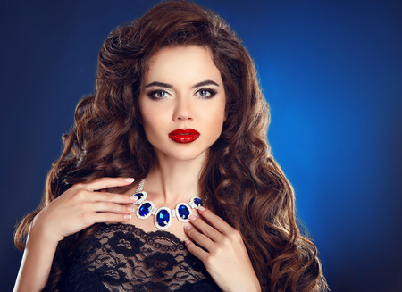 perming: Brunette girl with long shiny wavy hair and red lips makeup, fashion necklace jewelry. Beautiful model with curly hairstyle isolated on blue studio background.