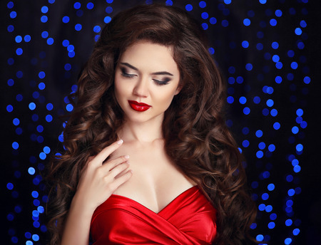 beauty salons: Makeup. Hair. Attractive brunette girl with healthy curly hairstyle and red lips, manicured nails. Beautiful woman isolated on party blue lights background.