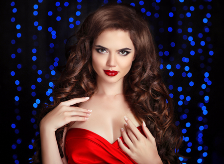 Makeup. Hair. Attractive brunette girl with healthy curly hairstyle and red lips, manicured nails. Beautiful woman isolated on party blue lights background. photo