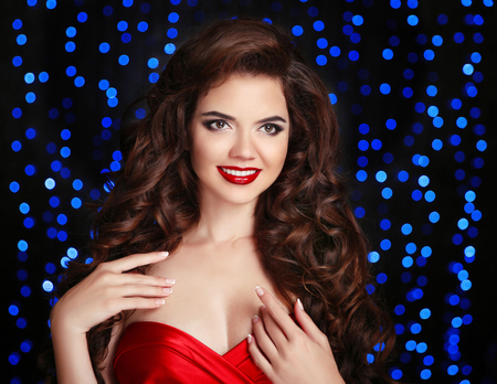 christmas perfume: Beautiful smiling girl. Makeup. Hairstyle. Happy brunette with red lips and long curly hair  isolated on party blue lights background. Woman studio closeup portrait. Stock Photo