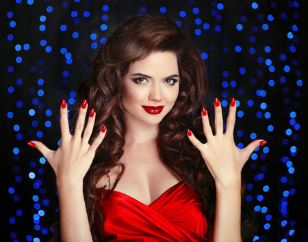 Manicured nails. Beautiful brunette girl with healthy curly hair style and red lips makeup. Elegant young woman in red showing ten fingers over party blue lights background. photo