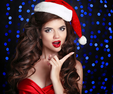 Surprised Santa girl with opened mouth. Beautiful smiling woman model in red hat over christmas blue lights background. Makeup. Healthy long hair style. photo