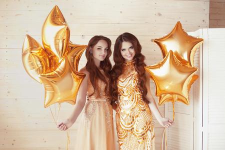 mujeres elegantes: señoras glamorosas partido, dos mujeres en la moda vestidos de oro con las estrellas brillantes globos. Celebracion. Fondo del feliz cumpleaños.