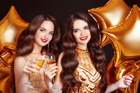 sexy party girl: Ladies clinking glasses, party Celebration. Happy women congratulations over golden stars balloons isolated on black background. Glam friends in golden dresses. Stock Photo