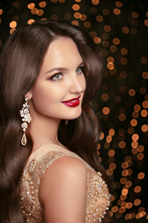 red hair beauty: Makeup. Jewelry. Beautiful smiling woman model with expensive golden earrings, brunette long wavy hair and red lips over holiday party lights background.  Beauty studio portrait. Stock Photo