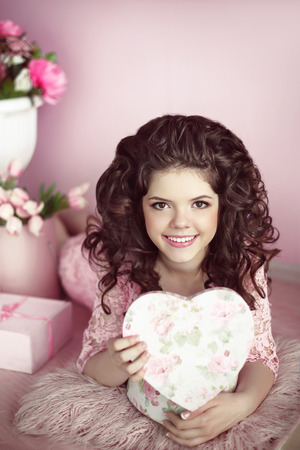 brunette girl: Beautiful young teen girl portrait open present, romantic surprise. Brunette in pink dress over bouquet of flowers and gift boxes lying on floor, indoor portrait. Pretty fun female.