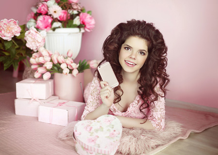 bunch of hearts: Beautiful young teen girl holding mobile phone. Brunette with flowers bouquet and gift boxes in pink dress lying on floor, indoor portrait. Pretty female.