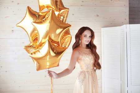 life style: Portrait of elegant happy woman in fashion dress holding golden star balloons over wooden beige background