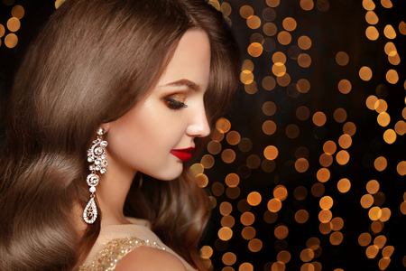 jewelry background: Makeup. Jewelry. Beautiful smiling woman model with expensive golden earrings, brunette long wavy hair and red lips over holiday party lights background.  Beauty studio portrait. Stock Photo