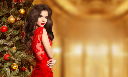 Young beautiful brunette woman in red dress on christmas with red lips, woman in holiday room with a Christmas tree and xmas balls, happy new year.