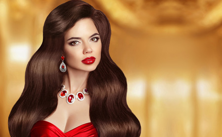 ruby red: Beautiful Hair. Brunette girl with long smooth shiny wavy hair. Hairstyle. Red lips makeup. Fashionable jewelry set, precious necklace and earrings. Glamour portrait.