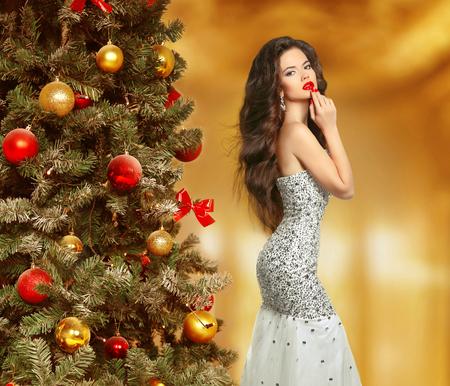 navidad elegante: Mujer hermosa de la moda en el vestir, elegante dama de árbol de Navidad decorado. Maquillaje de belleza. Peinado. Modelo de la chica morena en vestido de la sirena del glam que presenta sobre el fondo borroso. Foto de archivo