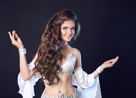 femme noire nue: Danse du ventre. sourire Belle femme danseuse du ventre portrait. Sexy arabian turc artiste professionnel oriental dans le carnaval brillant costume blanc avec de longs cheveux bouclés isolé sur fond noir. Banque d'images
