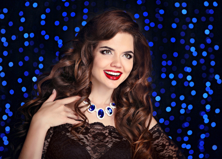 glamour hair: Beautiful laughing brunette. Happy smiling girl with long shiny curly hair and red lips makeup. Fashion gems jewelry. Glamour women posing on party blue lights background. Stock Photo