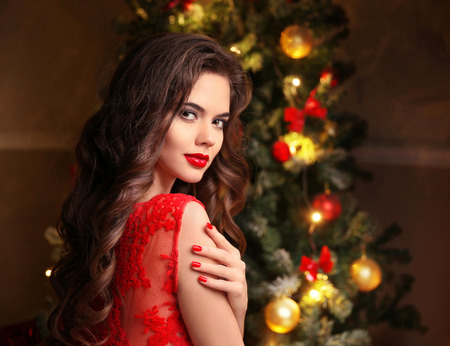 christmas manicure: Christmas manicure. Beautiful smiling woman portrait. Makeup. Healthy long hair style. Elegant lady in red dress over christmas tree lights background. Xmas Gifts. Stock Photo