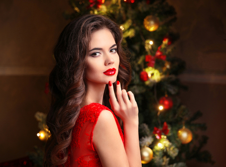 christmas manicure: Christmas. Beautiful smiling woman. Manicure nails. Makeup. Healthy long hair style. Elegant lady in red dress over christmas tree lights background. happy new year. Stock Photo