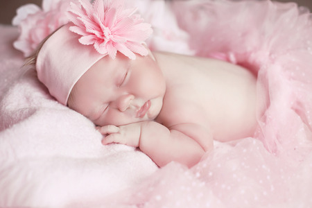 adorable child: Portrait of adorable sleeping baby girl over pink, infant child. Stock Photo
