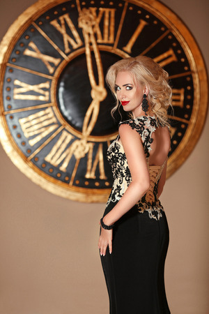 Elegant woman in fashion black dress, lady with makeup and blond hairstyle posing in front of wall clock, golden colors. Beauty indoor portrait photo. Stock Photo