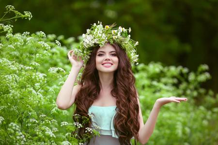 Portrait der jungen Frau im grünen Frühlingspark mit offenen leeren Handfläche der Hand für Kopie Raum lächelnd. Schöne Frau mit dem gesunden langen lockigen Haaren posiert im Freien. Standard-Bild