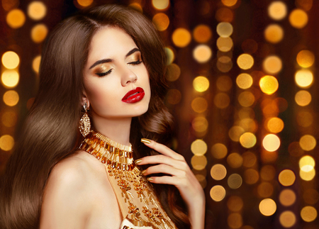 sexy glamour: Elegant sexy girl portrait in gold. Makeup. Fashion earrings jewelry. Long wavy hair. Beautiful glamour woman in fashionable dress posing over golden party lights boker background. Stock Photo