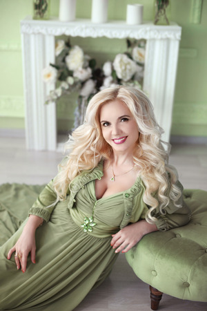 wall decor: Beautiful smiling blond woman with long curly hair style wears in green dress posing on the floor over decor flowers wall, home interior.