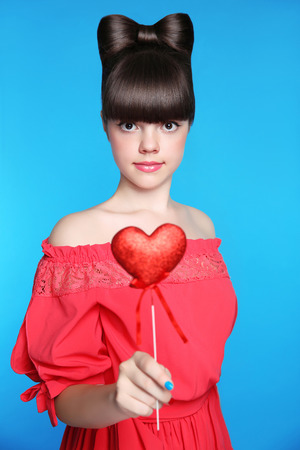 Smiling teen girl with bow hair style, brunette young model holding red heart isolated in blue background. studio portrait