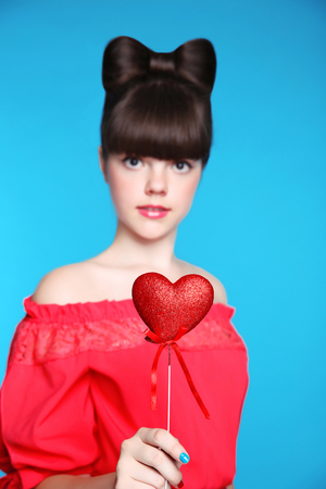 Red heart in teen girl hand. Brunette young model  with bow hair style,  isolated in blue background.