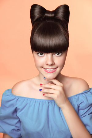 female beauty: Beautiful smiling teen girl with bow hairstyle, makeup and colourful manicured polish nails. Funny girl in blue dress showing manicure fingers isolated on studio background. Stock Photo