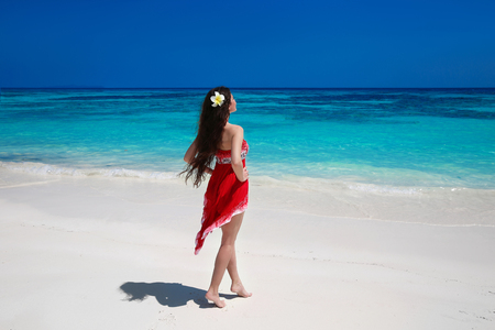 summer dress: Beautiful free young woman relax on the exotic sea, brunette smiling girl in red dress on tropical beach with white sand. Enjoyment. Lifestyle. Freedom. Good life. Travel.