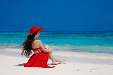 girl in a hat: Fashion carefree woman in hat enjoying exotic sea, brunette relax on tropical beach at summer holiday. Attractive girl in red dress resting. Bliss freedom concept. Stock Photo
