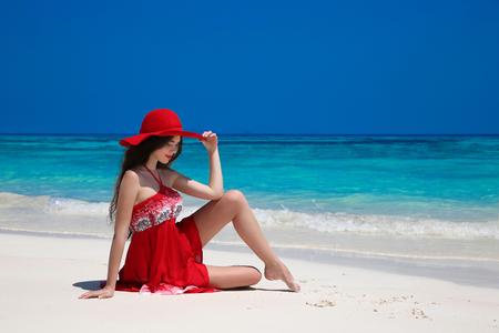 Schöne unbeschwerte Frau im Hut auf exotischen Meer zu genießen, Brunette auf tropischen Strand auf den Sommerurlaub entspannen. Attraktive Mädchen im roten Kleid ruht. Bliss Freiheit Konzept. Standard-Bild