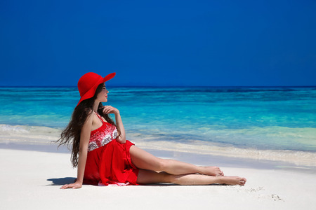 sea beach: Healthy lifestyle. Beautiful carefree woman in hat enjoying exotic sea, brunette lying on tropical beach at summer holiday. Attractive girl in red dress resting. Bliss freedom concept.