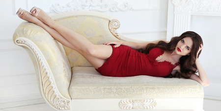 Beautiful brunette sexy woman in elegant red dress lying on modern sofa. Fashion model with long legs posing in white interior. Makeup. Wavy hair style. Stock Photo