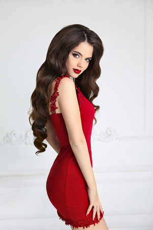 Elegant brunette sexy woman in fashion red dress. Attractive girl model with red lips makeup, long wavy hair style isolated on white background.
