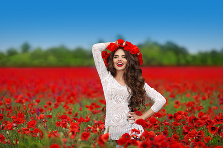 Hair. Beautiful happy smiling teen girl portrait with red flowers on head enjoying in poppies field nature background. Carefree woman. Wellness well-being happiness concept. Archivio Fotografico